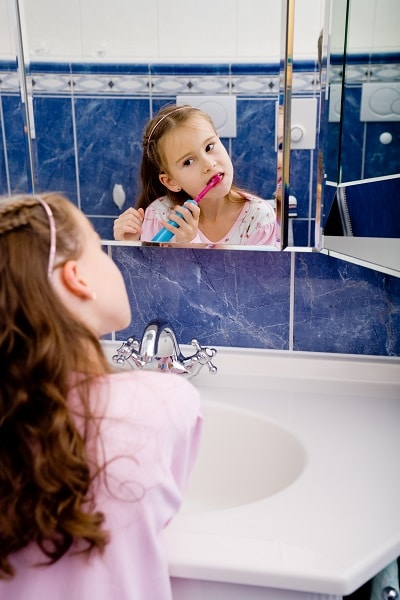 Girl using electric toothbrush